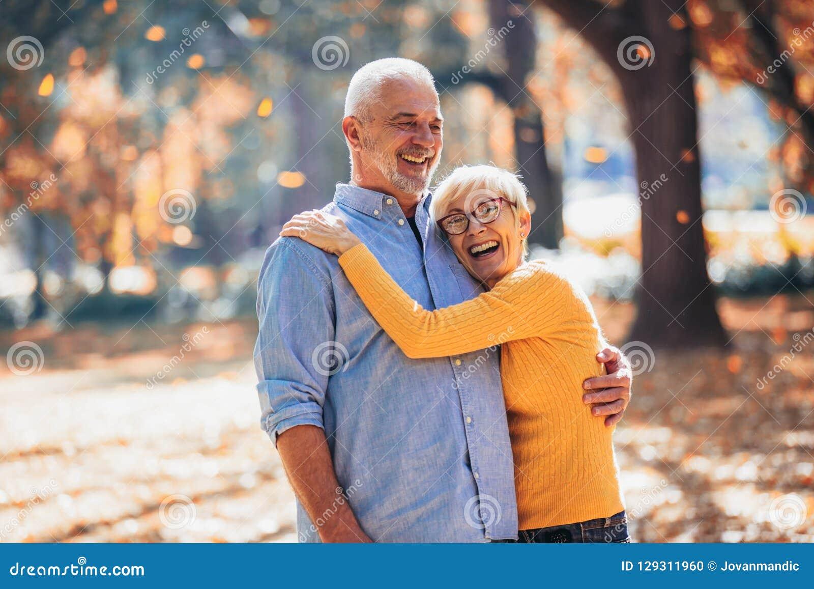 Pensionärer på en gå i höstskog