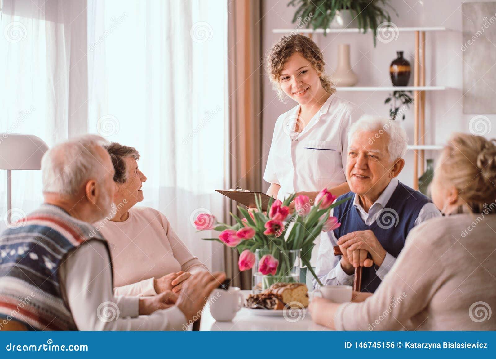 Pensionati a casa di riposo che parlano durante lo spuntino di pomeriggio
