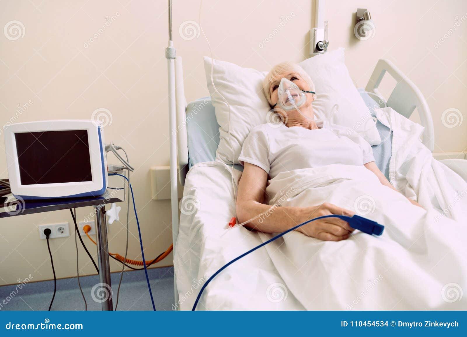 Pensionerad dam som ligger i sjukhussäng med respiratorisk service