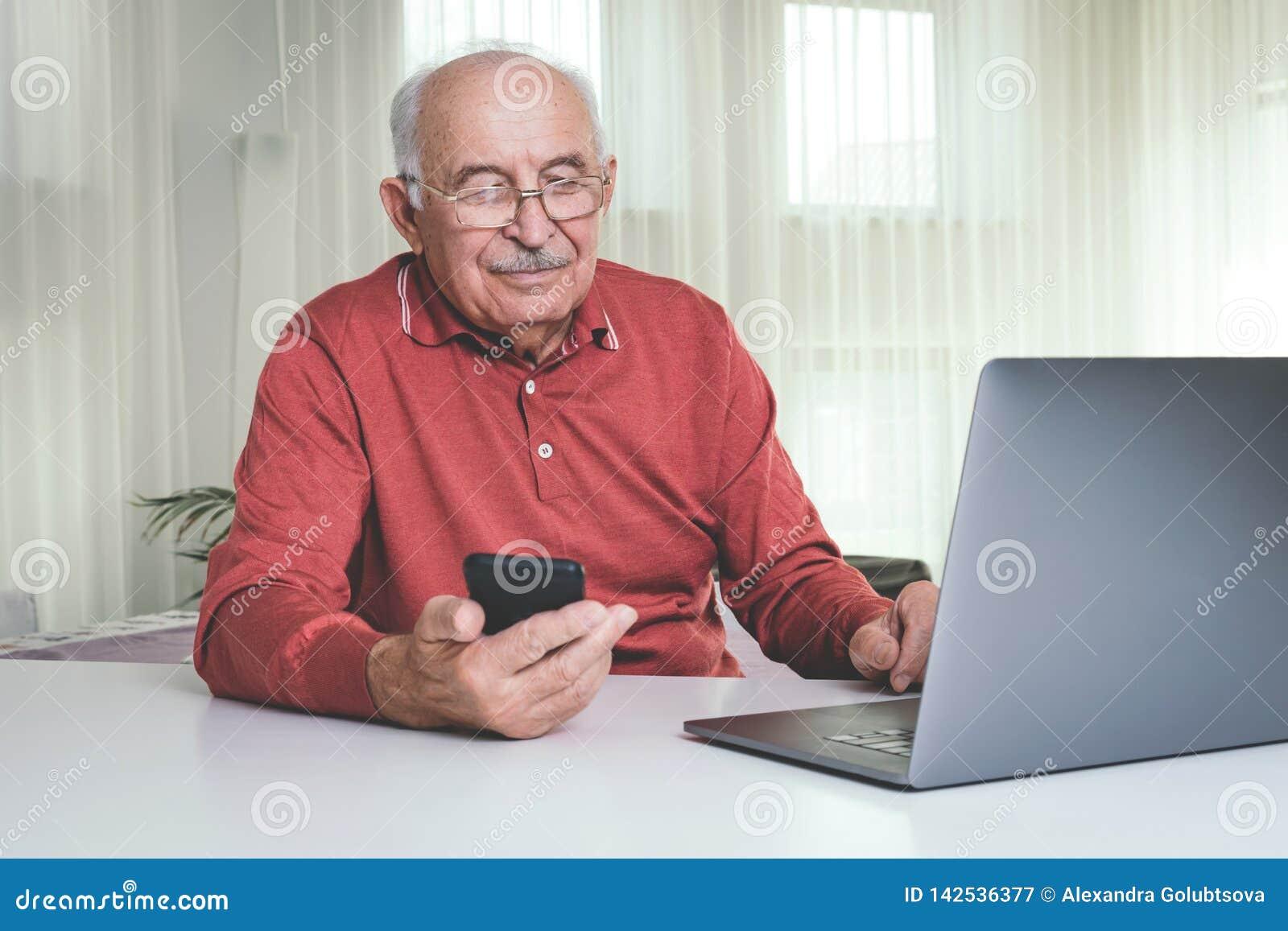 Pensionerad man som hemma använder datatekniker