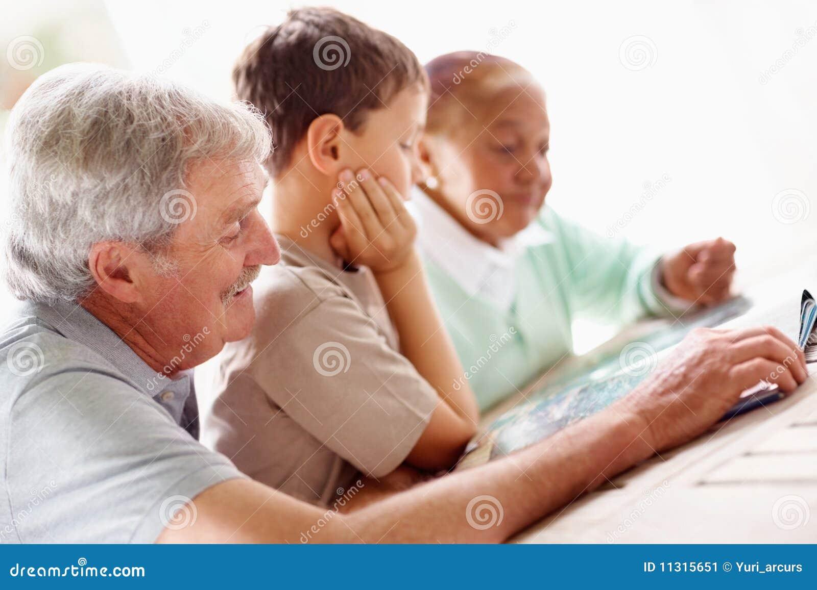 Pensionierter Mann, Der Ein Buch Mit Enkel Liest Stockbild