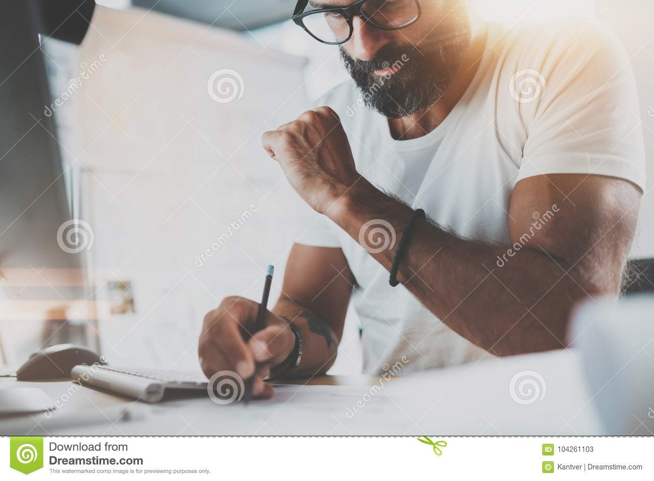 Pensive bearded designer wearing eye glasses and white tshirt, working at modern loft studio-office.Man drawing scetches