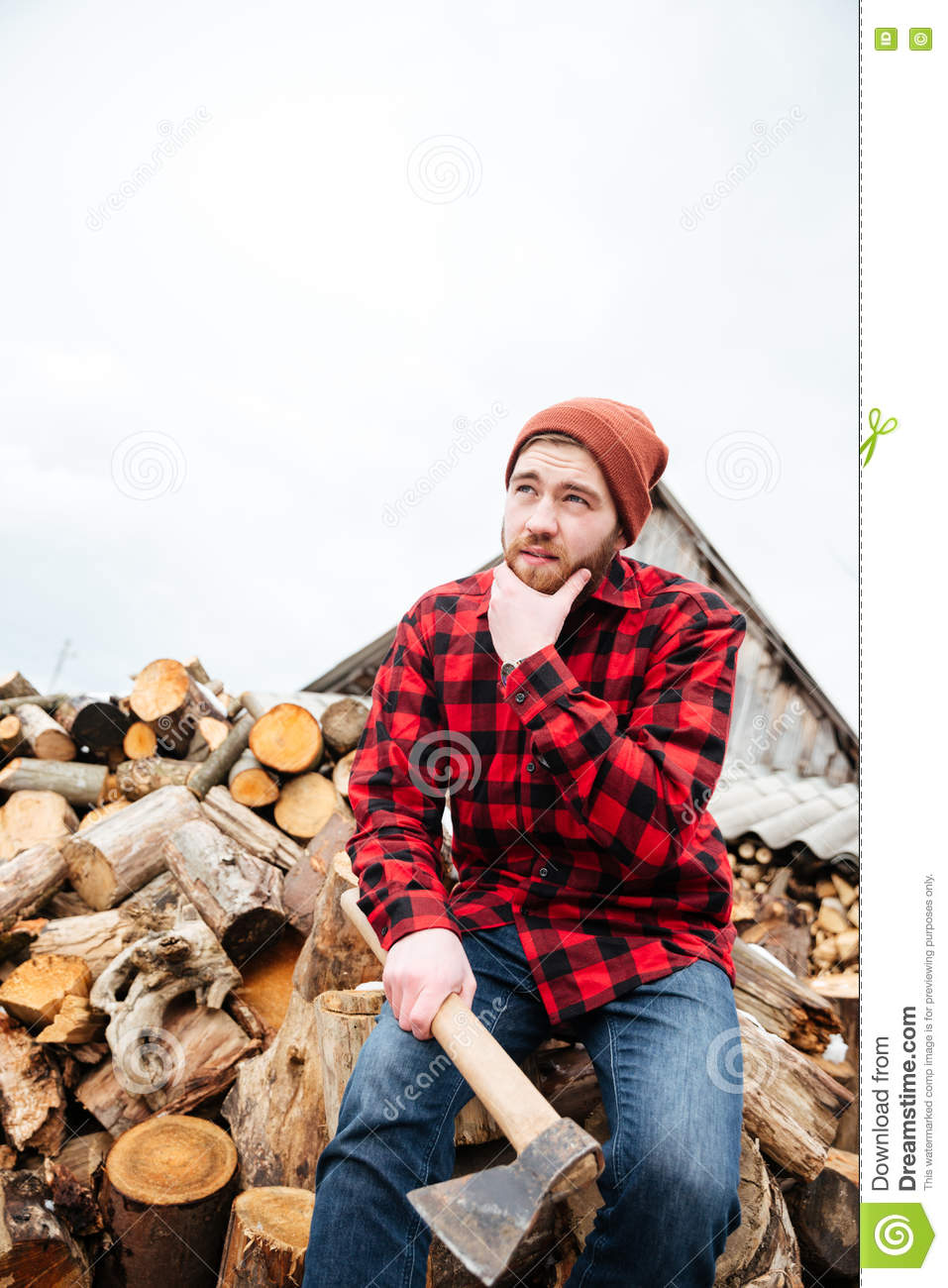 f0f42cedbb1 Pensive bearded young man in plaid shirt and hat with axe sitting on logs  and thinking