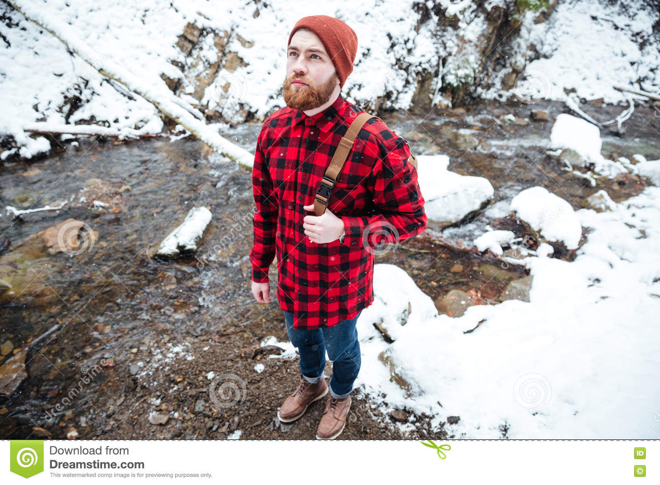 Pensive bearded young man standing near mountain river in winter