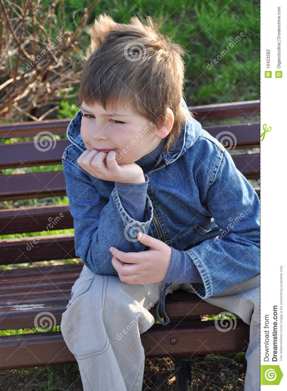 Pensive Boy Sitting On A Park Bench Stock Photography