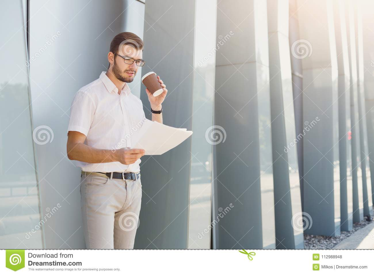 Pensive businessman reading the documents outdoors