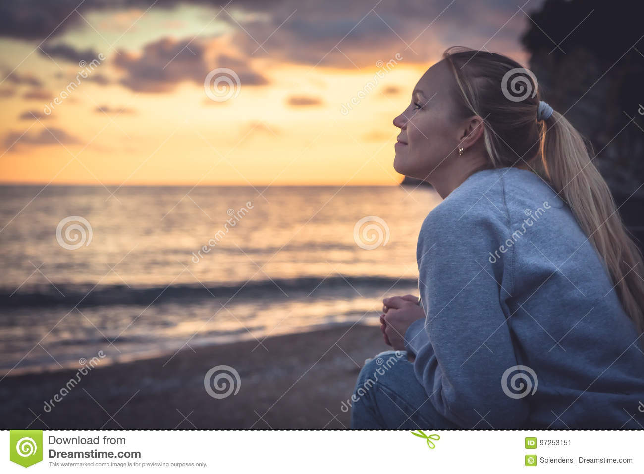 Pensive lonely smiling woman looking with hope into horizon during sunset at beach