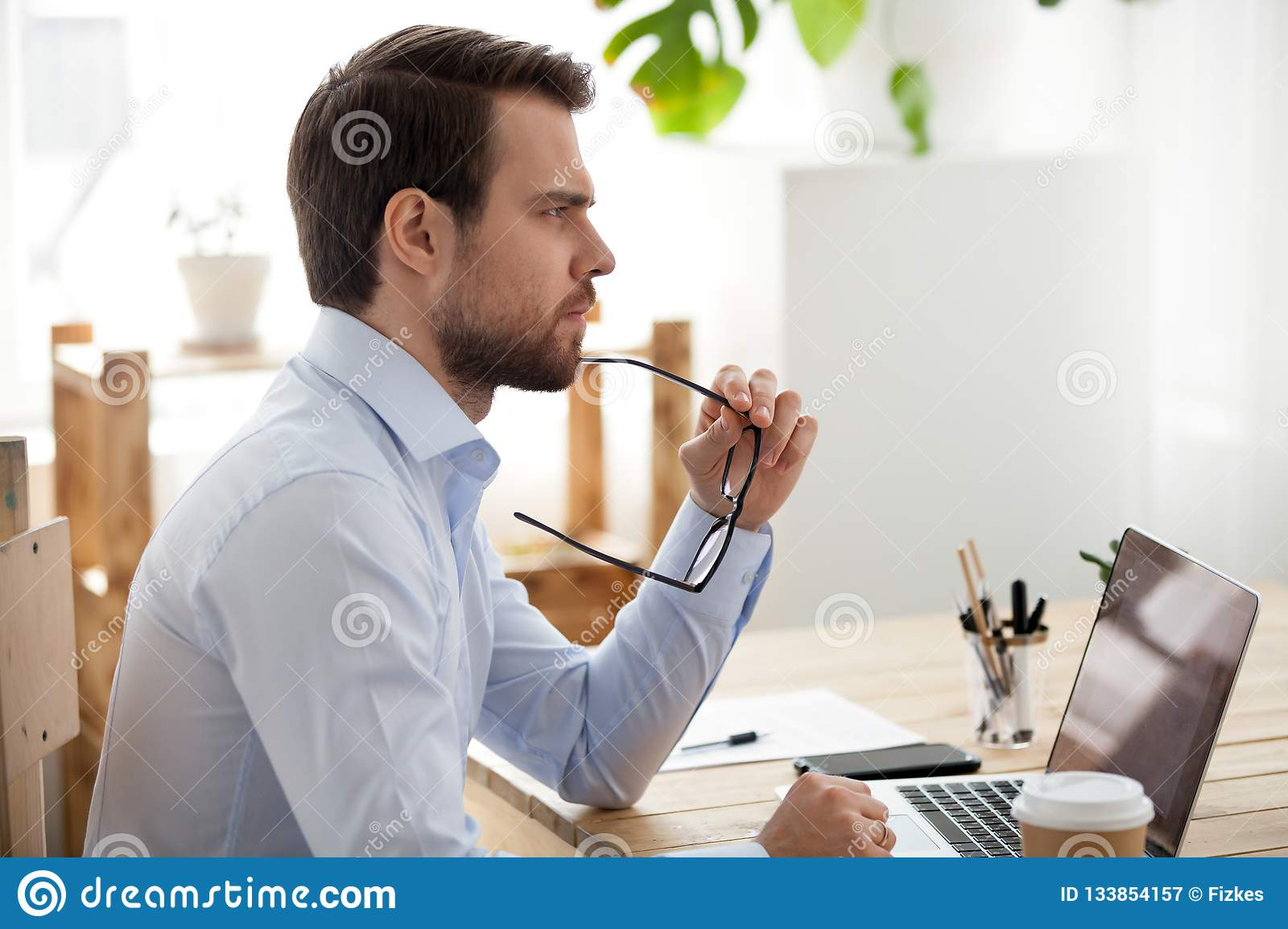 Pensive male employee think of problem solution