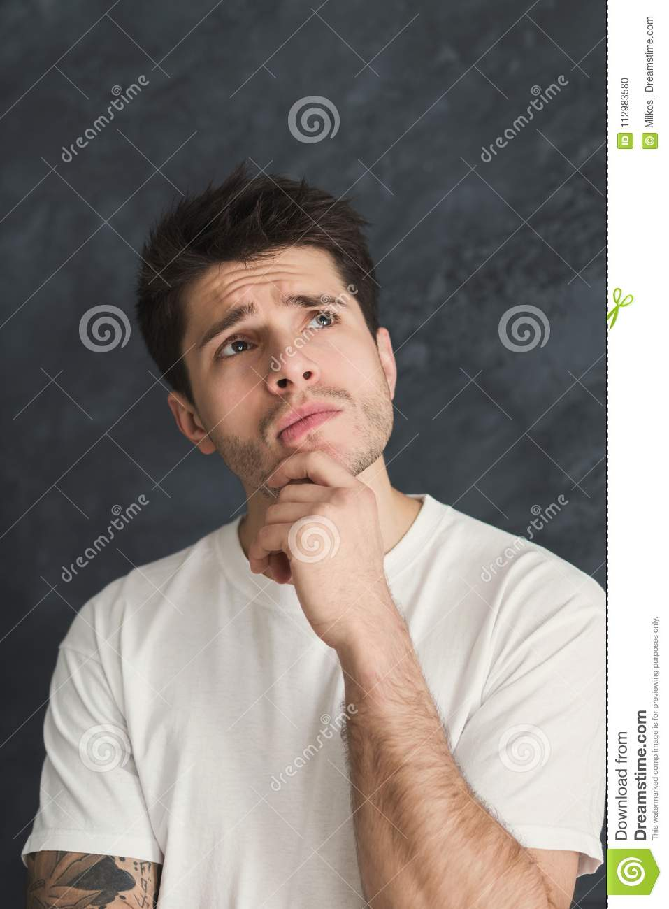 Pensive man posing with hand on chin