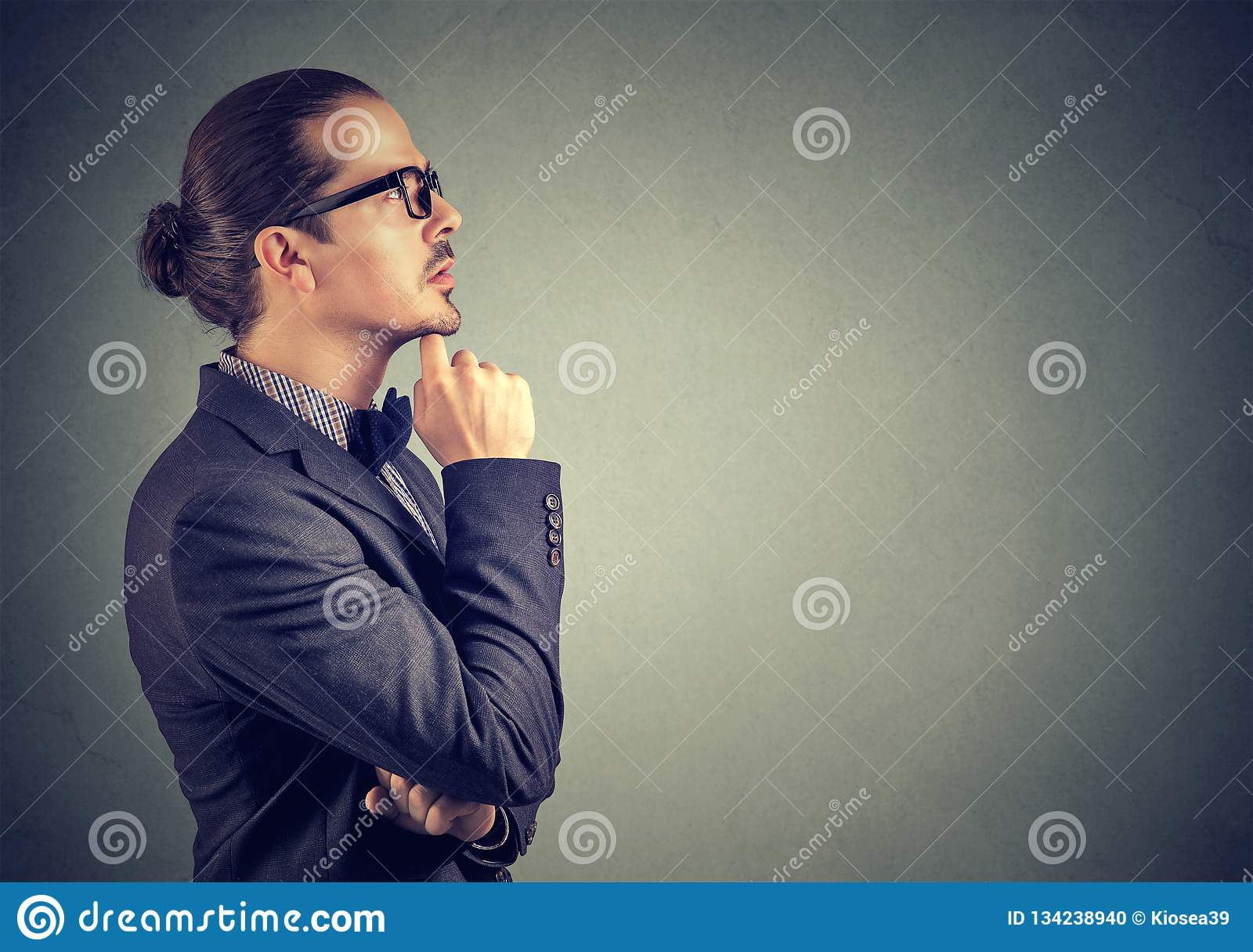 Pensive man touching lips while remembering