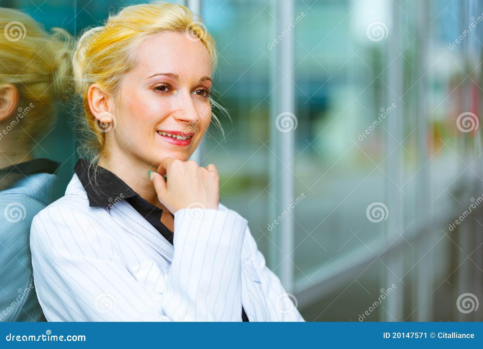 Pensive modern business woman near office building