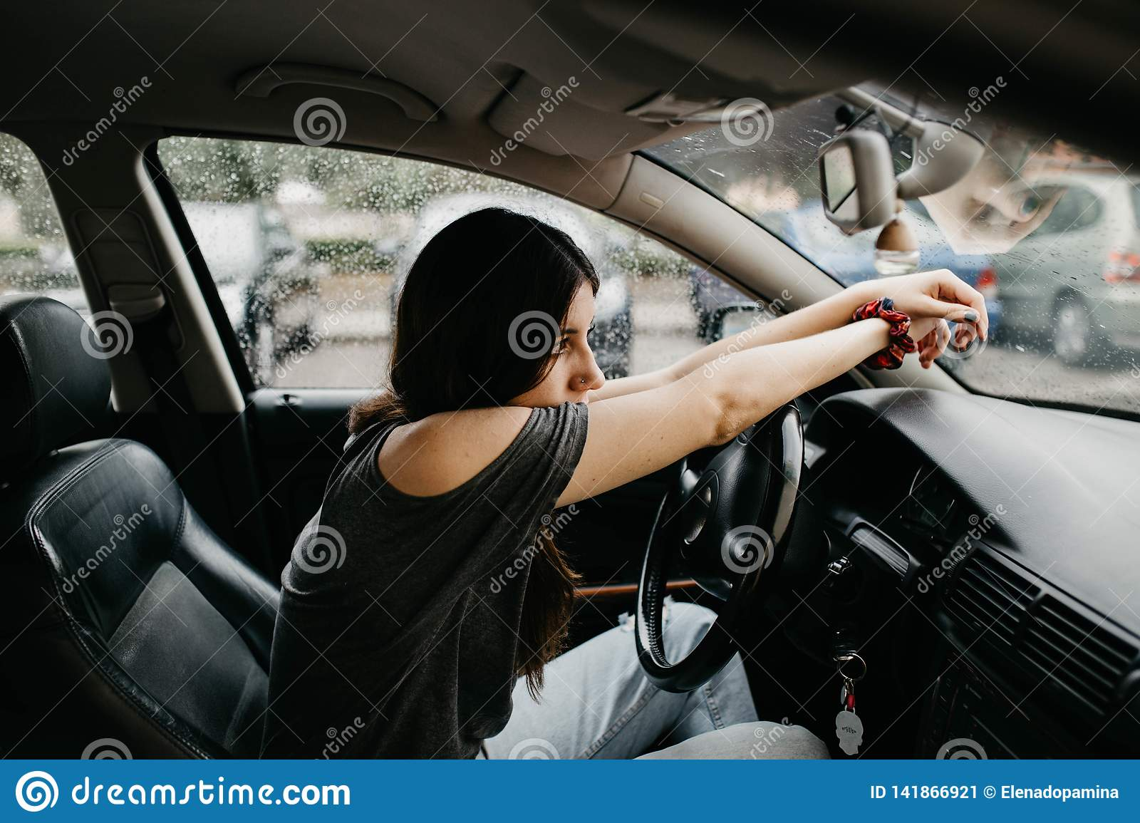 Pensive and sad young woman with arms on the steering wheel of the car on a rainy day