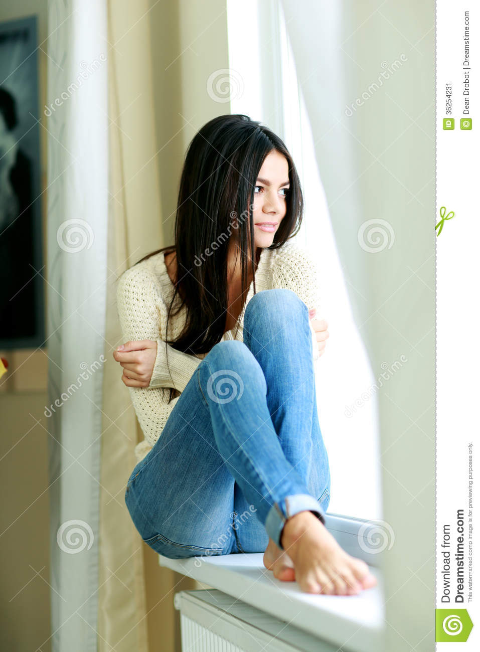 Pensive Woman Sitting On A Window Sill And Looking Outside