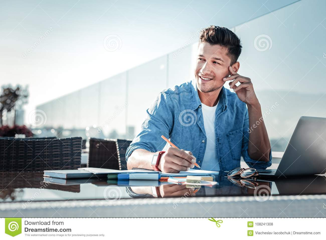 Pensive young gentleman smiling while working on laptop outdoors
