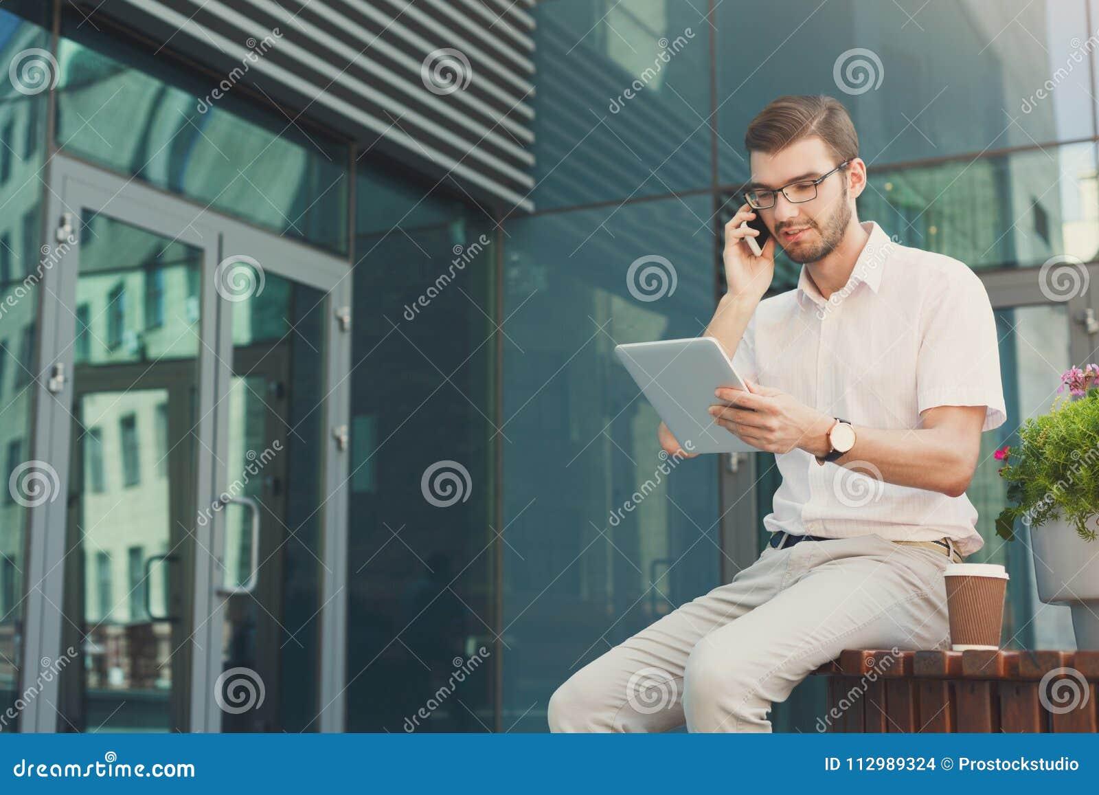 Thoughtful businessman multitasking outdoors