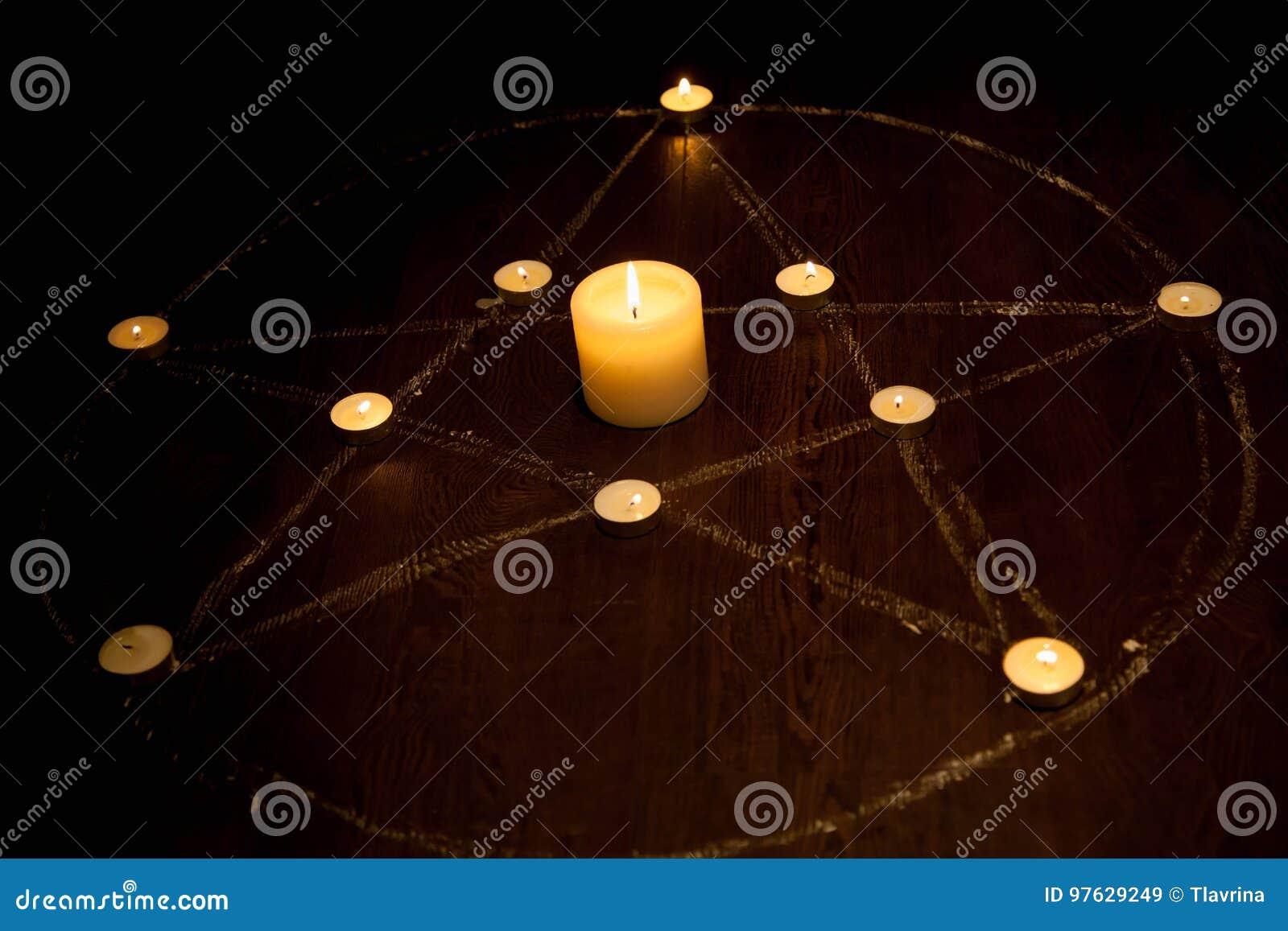 Pentagram místico con las velas encendidas en oscuridad, en fondo de madera