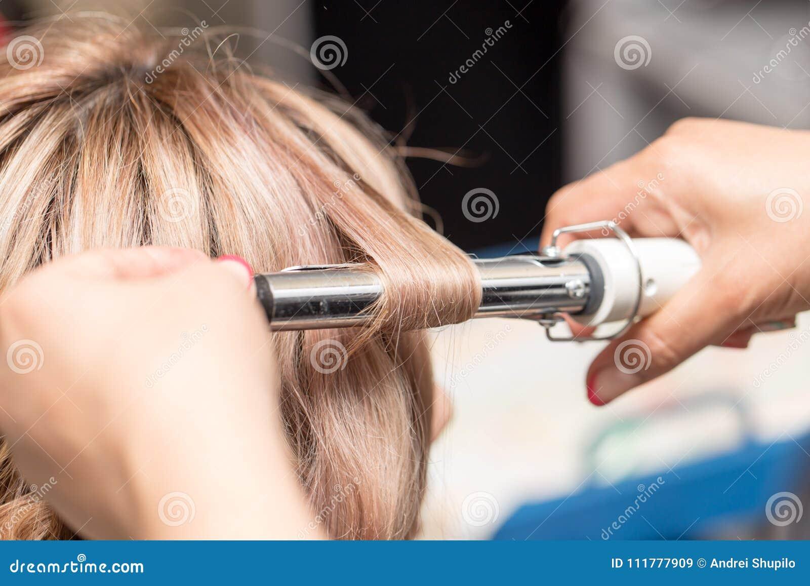 Penteados fêmeas na ondulação em um salão de beleza