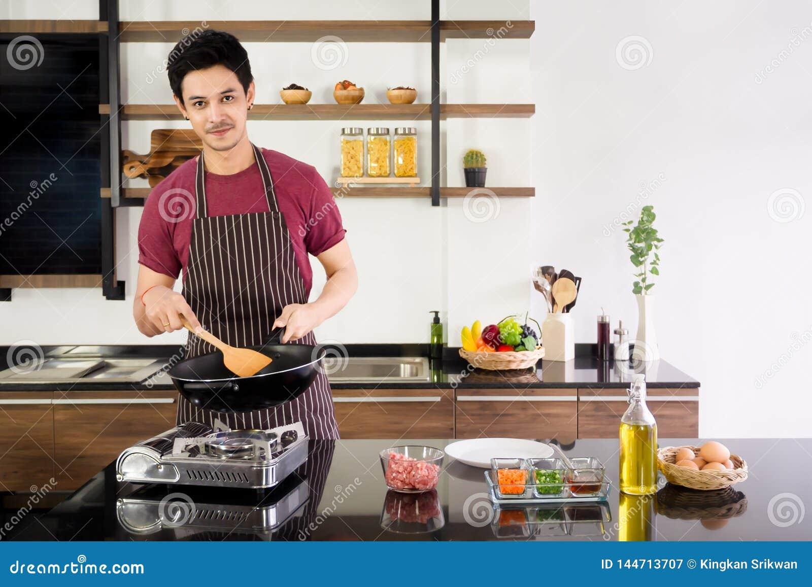Pentola attraente della tenuta del giovane e spatola di legno per produrre omelette per la prima colazione alla cucina moderna di