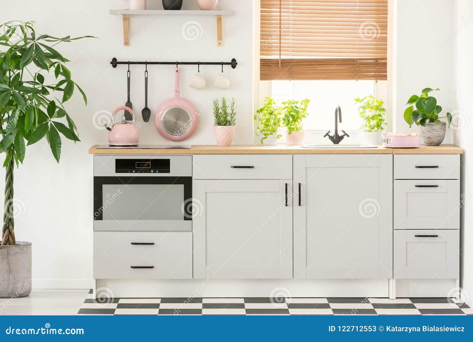 Pentola e bollitore in un bello interno della cucina con gli armadietti semplici e bianchi e lavandino di rosa pastello dalla fin