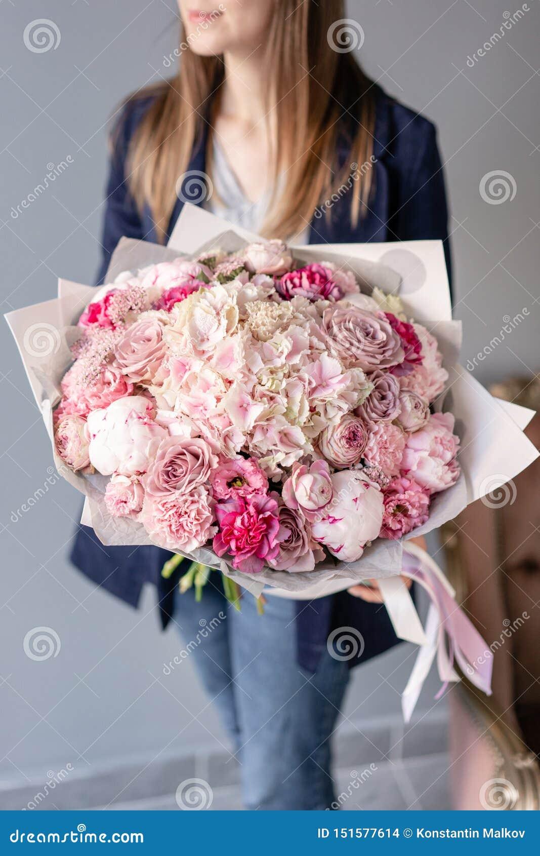 Peonías y hortensia rosadas Ramo hermoso de flores mezcladas en mano de la mujer Concepto floral de la tienda Fresco hermoso