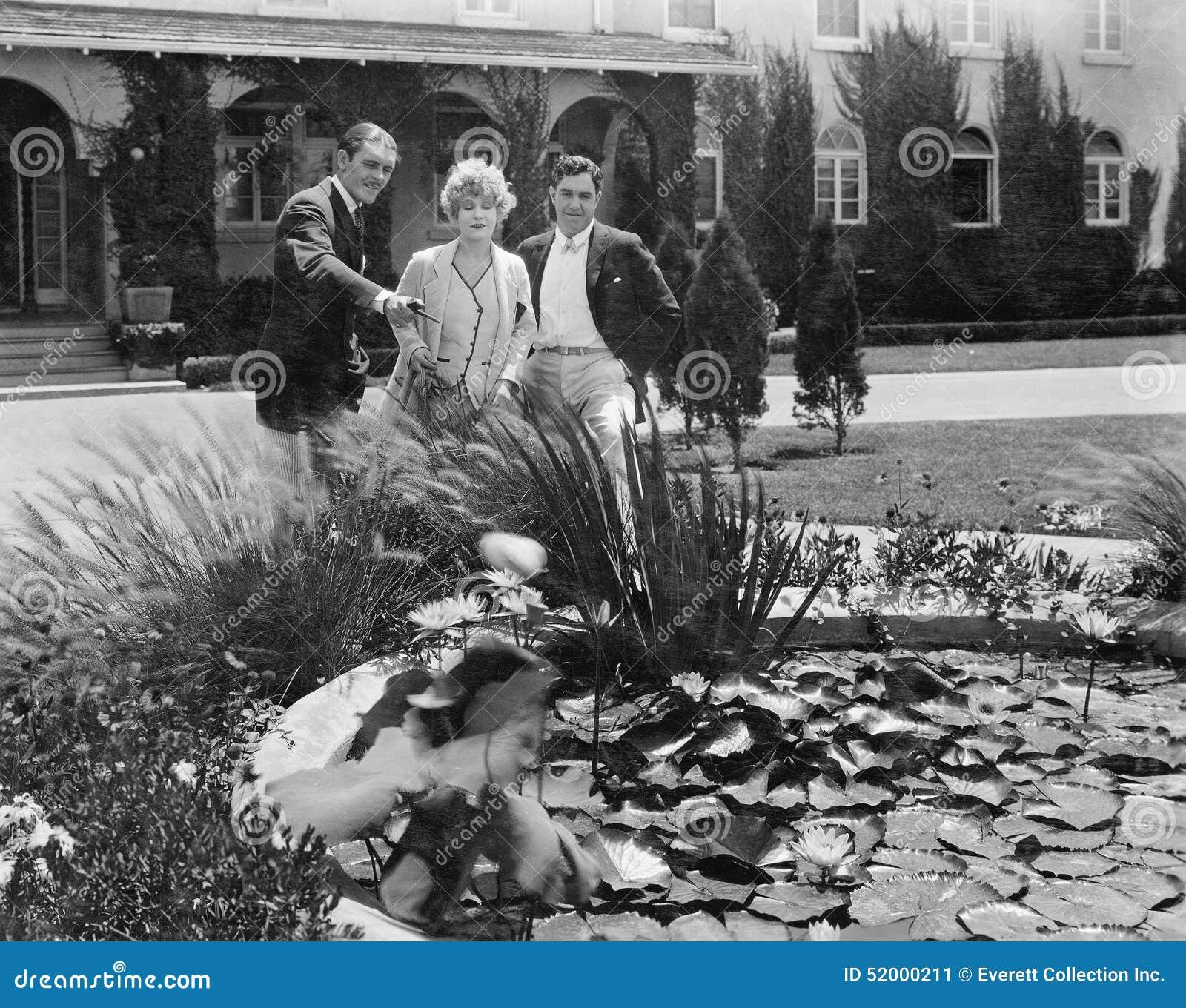 People admiring plants in pond in garden