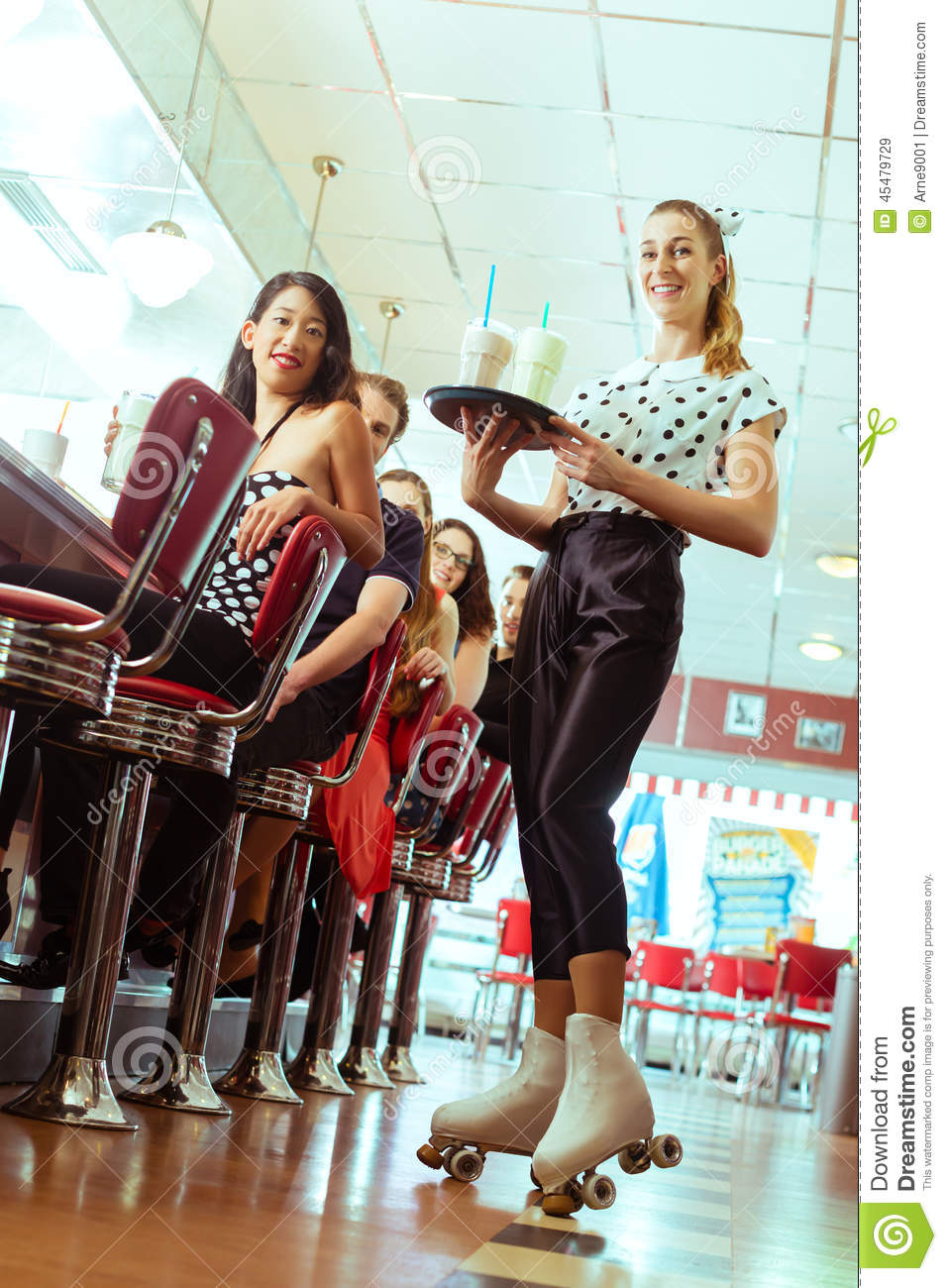 People In American Diner Or Restaurant With Waitress Stock