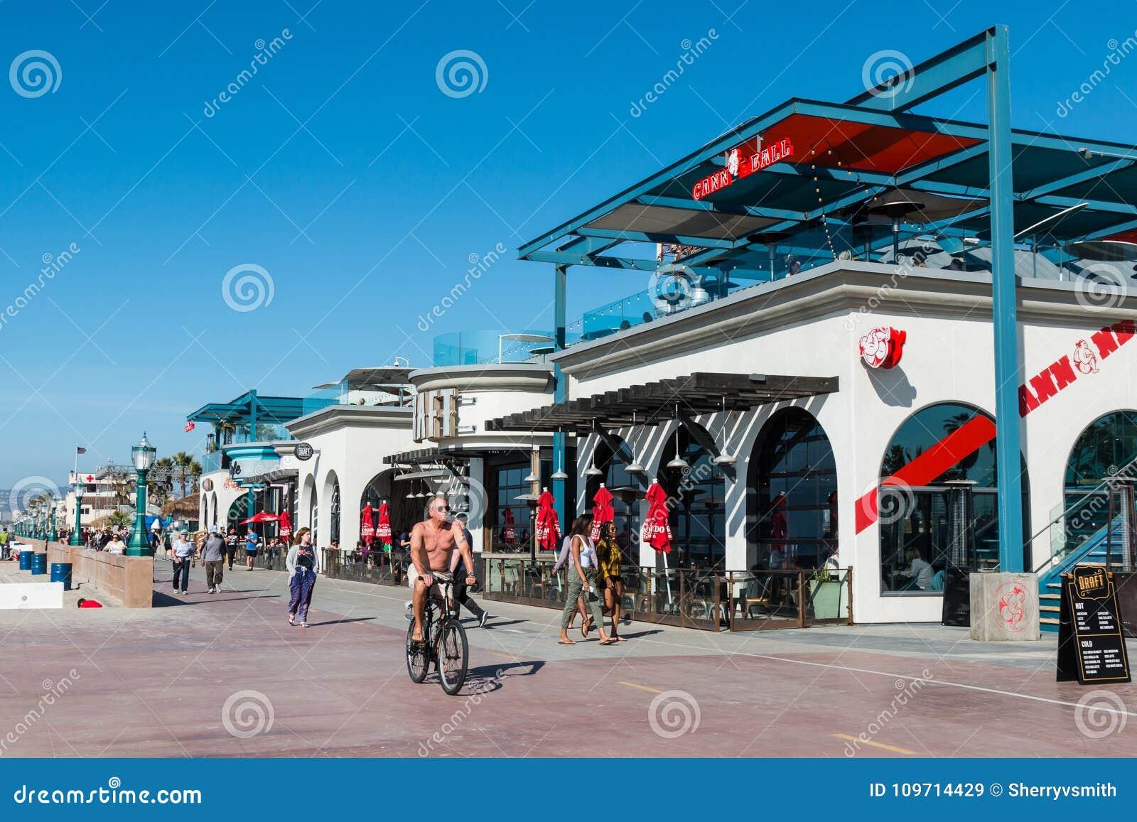 People Bike And Walk Along Mission Beach Boardwalk In San