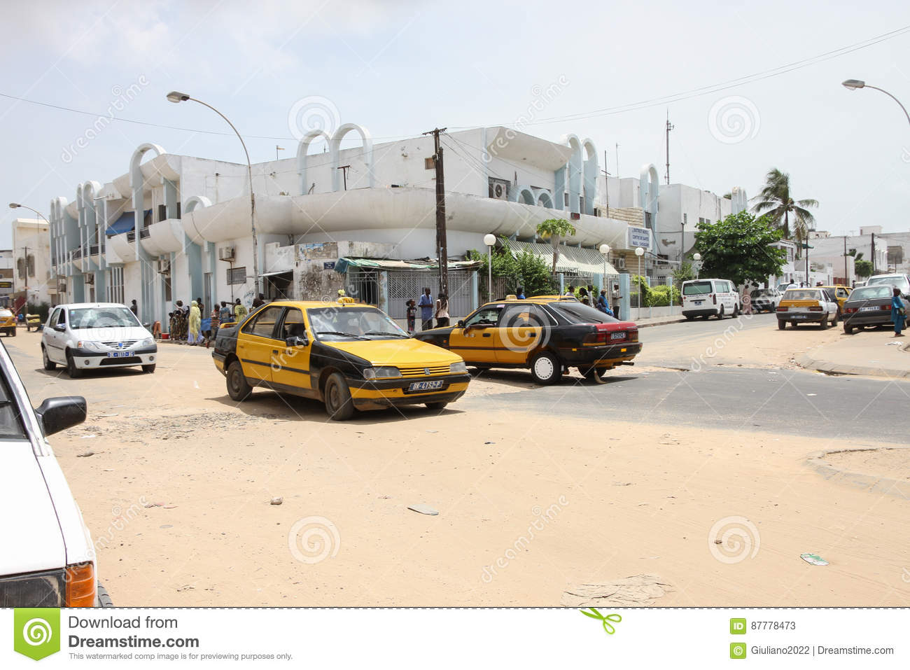 People and cars in a sandy street in the city of dakar in for Garage patte d oie