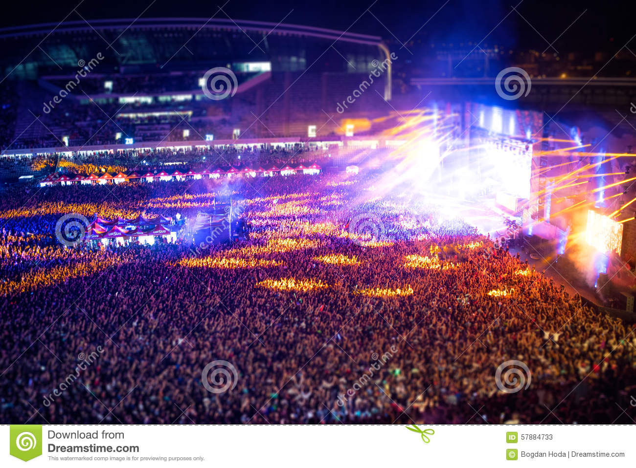 People clapping at night concert, partying and raising hands for the artist on stage. Blurry aerial view of concert crowd