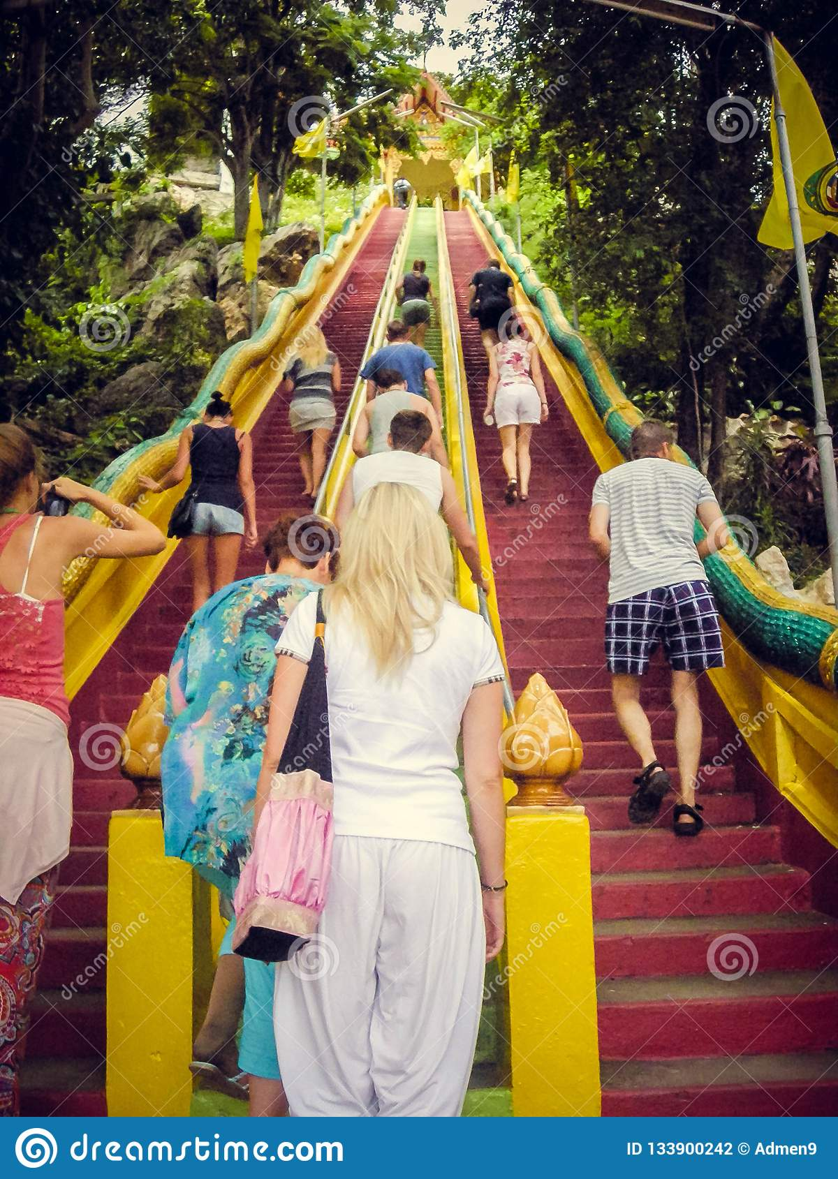 People climb up the red stairs up in Thailand. Tourism