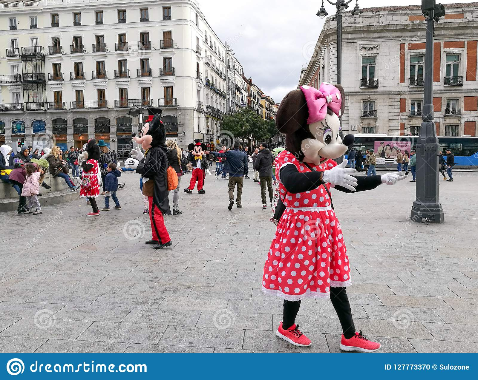 People in costumes of Minnie and Mickey Mouse are walking to entertain tourists.