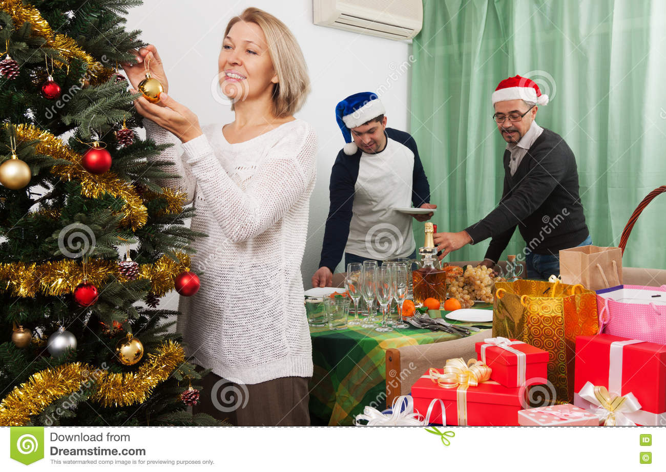 People Decorating For Christmas people decorate christmas tree stock photo - image: 72526094