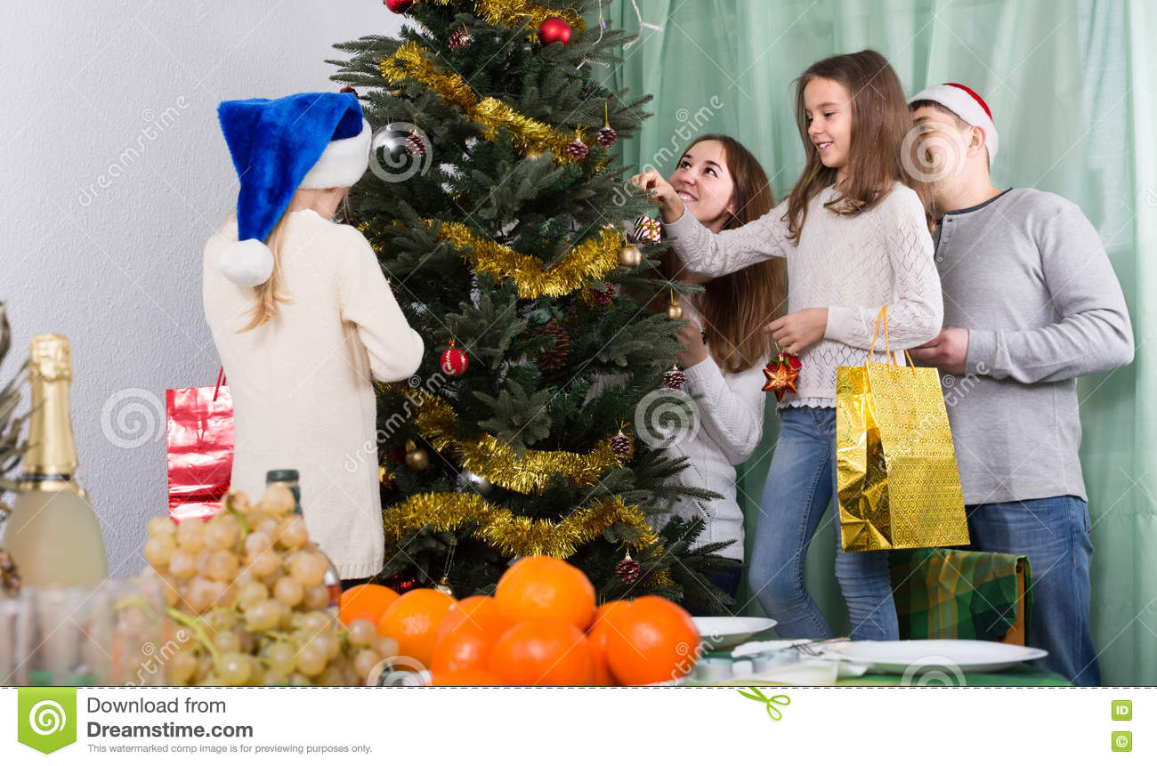 People Decorating For Christmas people decorating christmas tree stock photo - image: 77589771