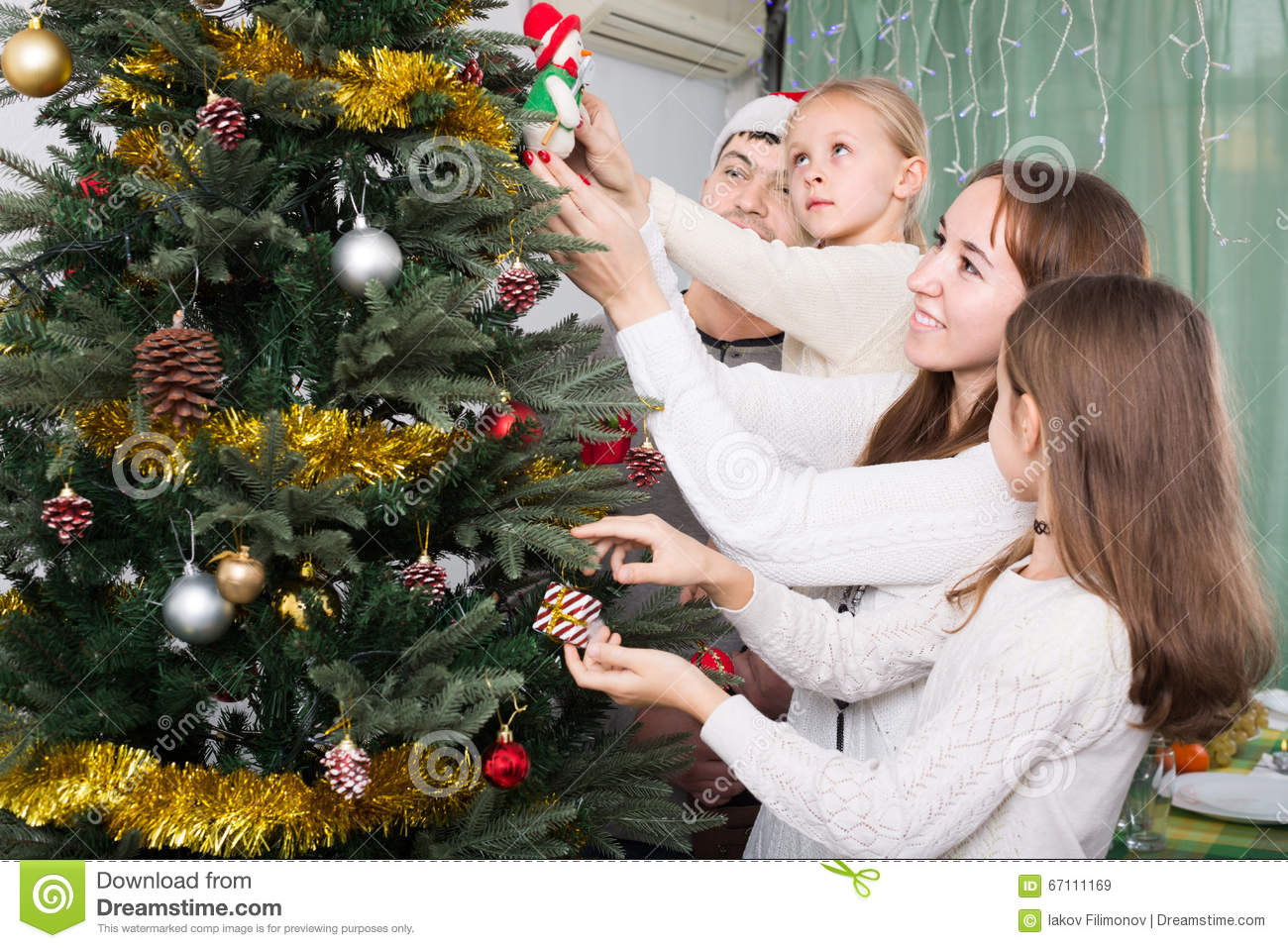 People Decorating A Christmas Tree people decorating christmas tree stock photo - image: 67111169
