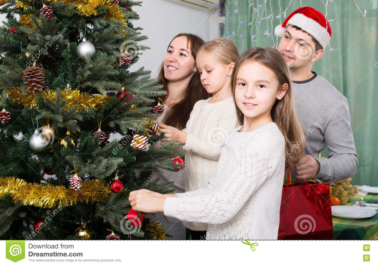 People Decorating For Christmas people decorating christmas tree stock photo - image: 73556087