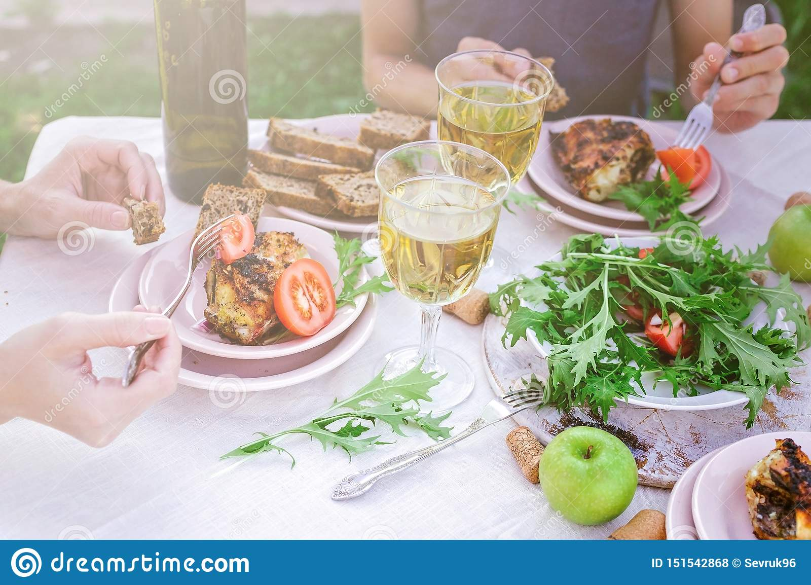 People eat in the garden at the table. Dinner concept with wine in the fresh air. Grilled sea fish and salads with vegetables and