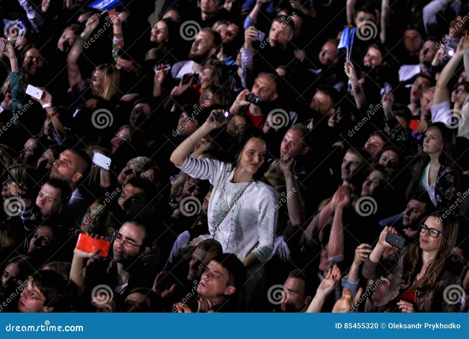 People enjoy rock-concert at a stadium