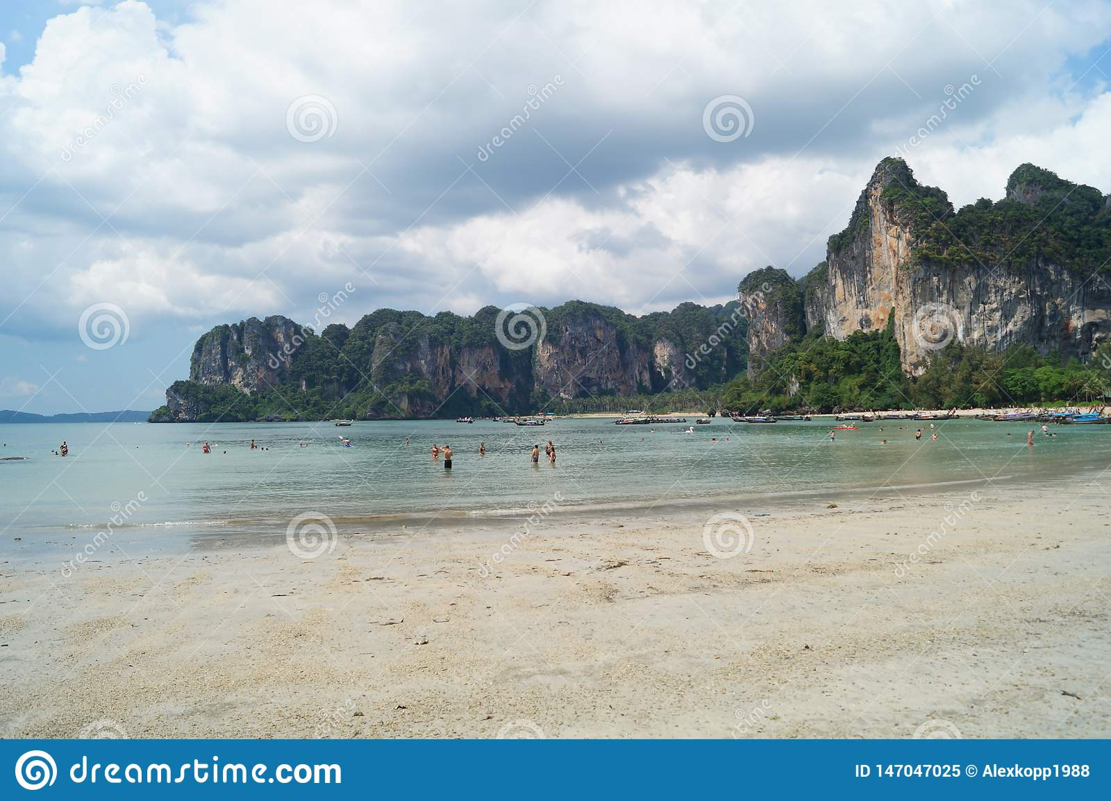 People enjoying the blue sky and the turquoise beach with rocks in Krabi, Thailand