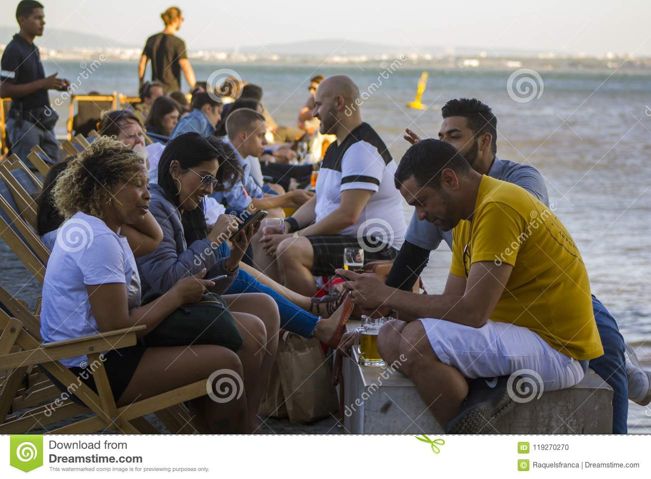 People enjoying a drink near the river