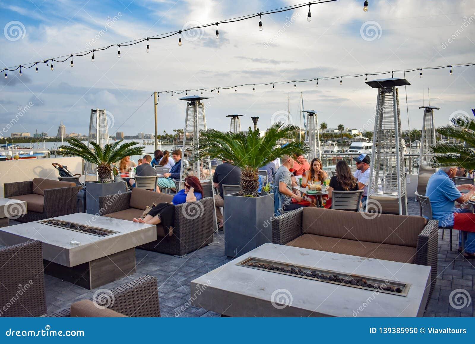 People Enjoying Seafood In Restaurant Terrace Area In