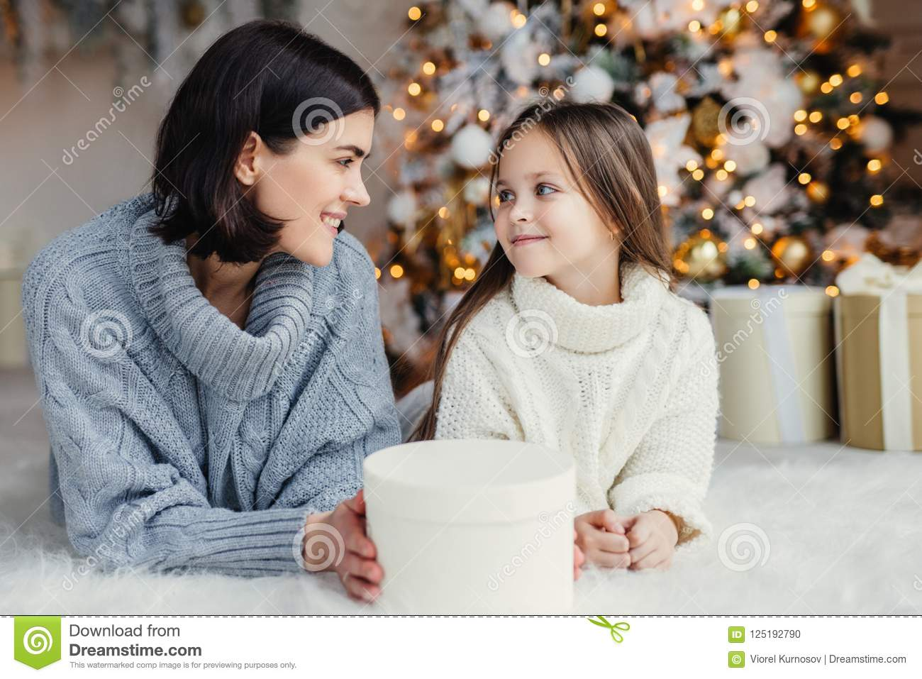 People, family, celebration and holidays concept. Mother and daughter with attractive appearance look at each other`s eyes, lie o