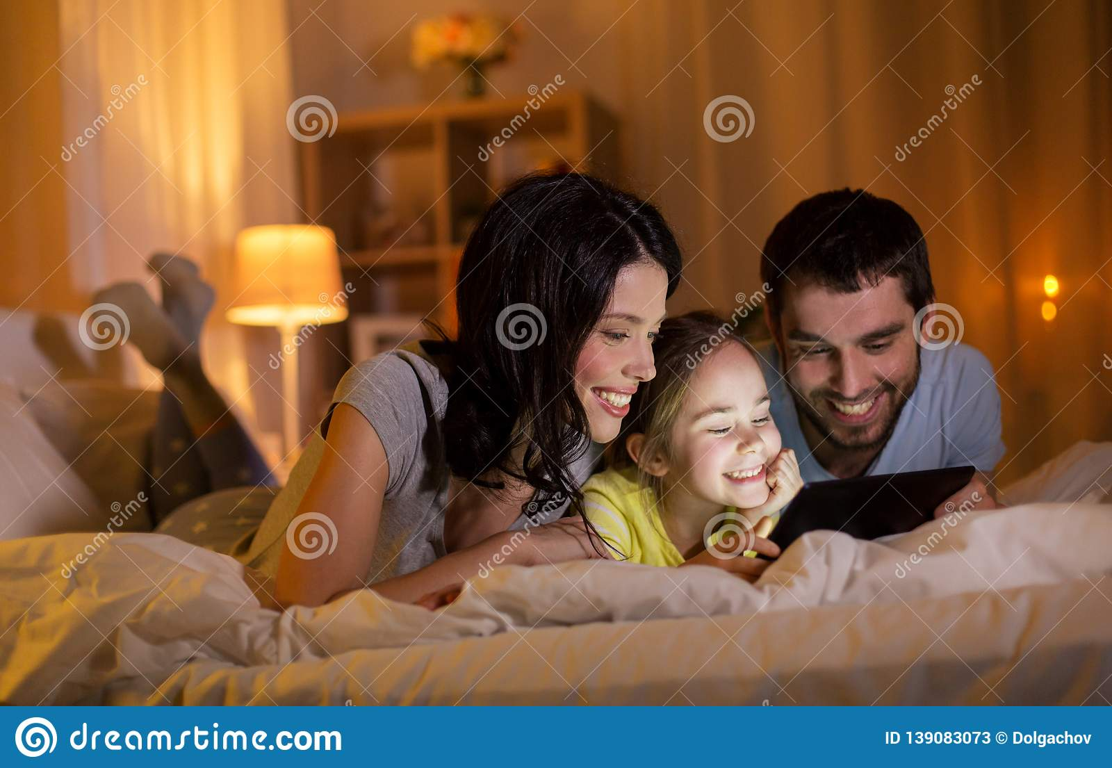 Family with tablet pc in bed at night at home