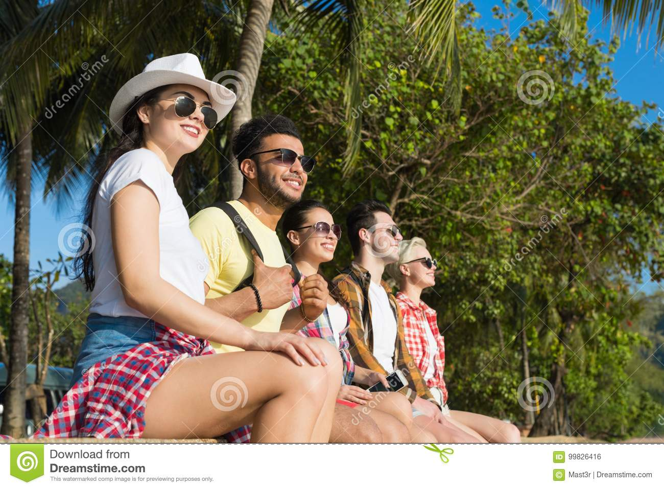 People Group Sitting Under Palm Trees In Park On Beach, Casual Friends Wear Sunglasses Happy Smiling Tourists