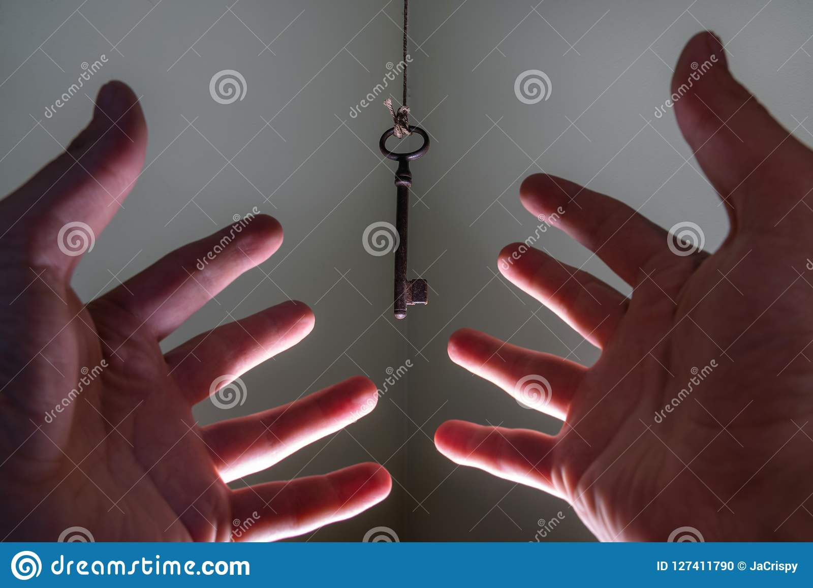 People hands reaching for vintage key hanging on a string. Business success freedom concept concept for aspirations, achievement