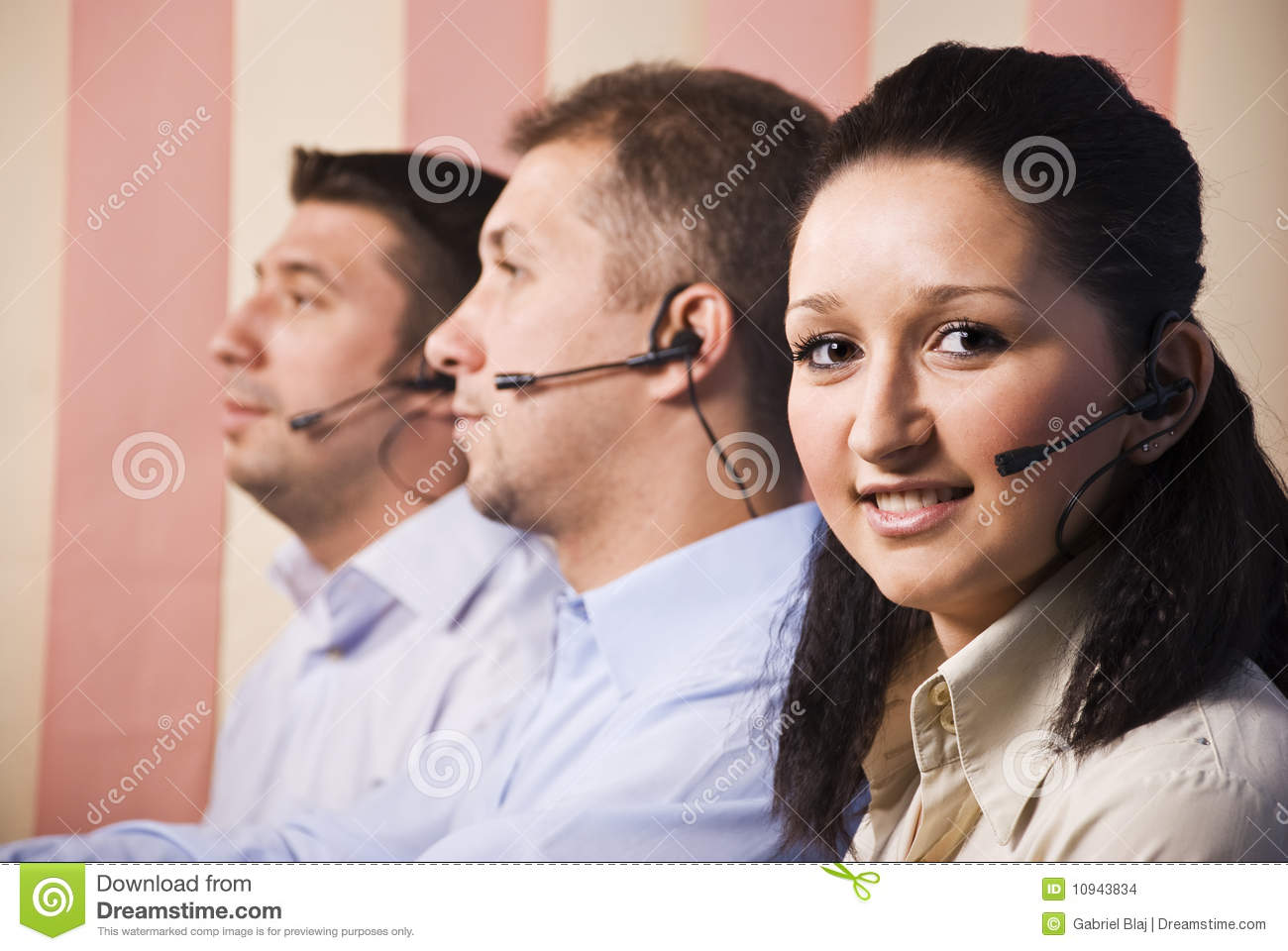 People with headset working in a call centre young woman facing and