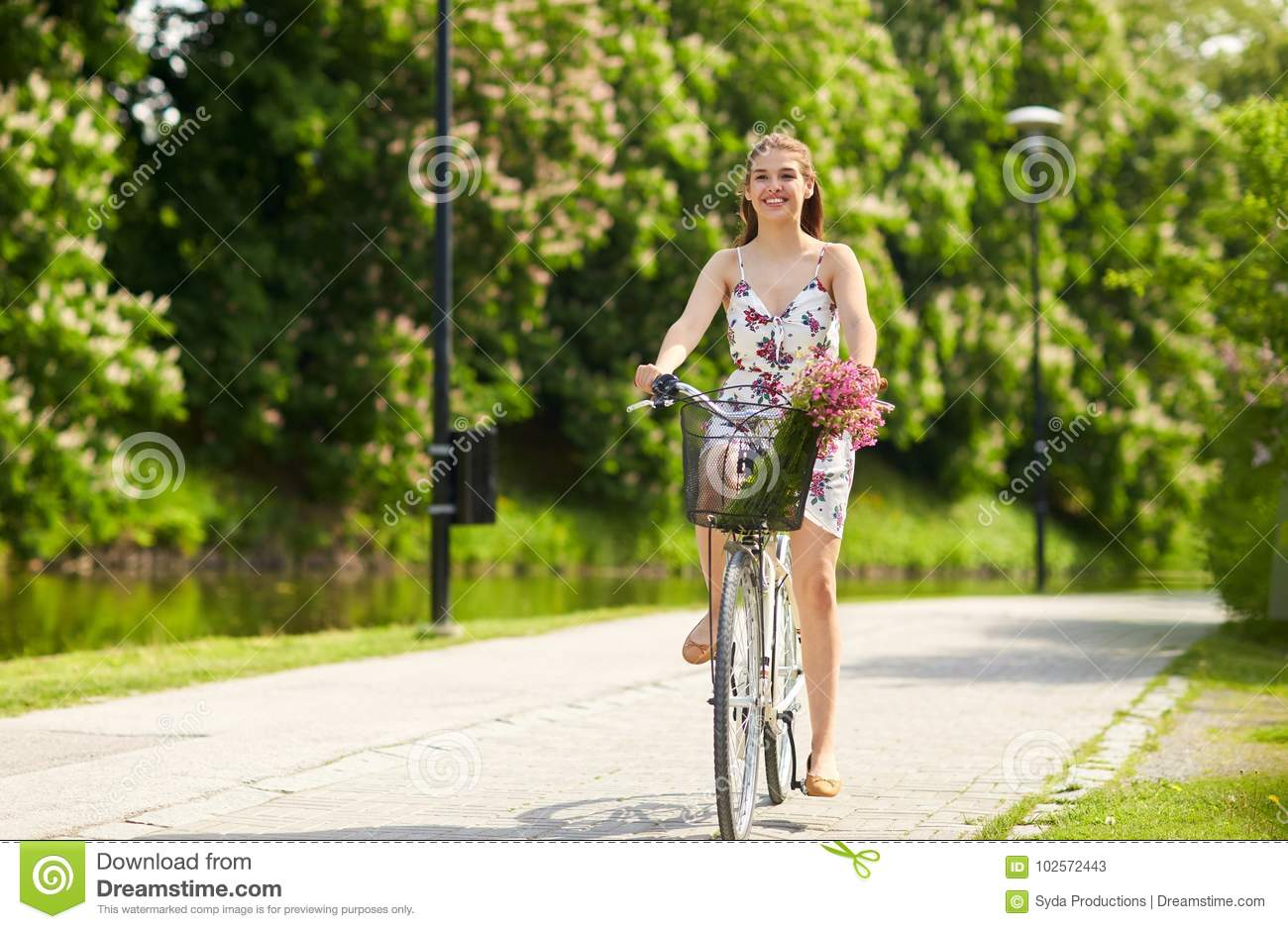 1e093c6599 Royalty-Free Stock Photo. Happy woman riding fixie bicycle in summer park