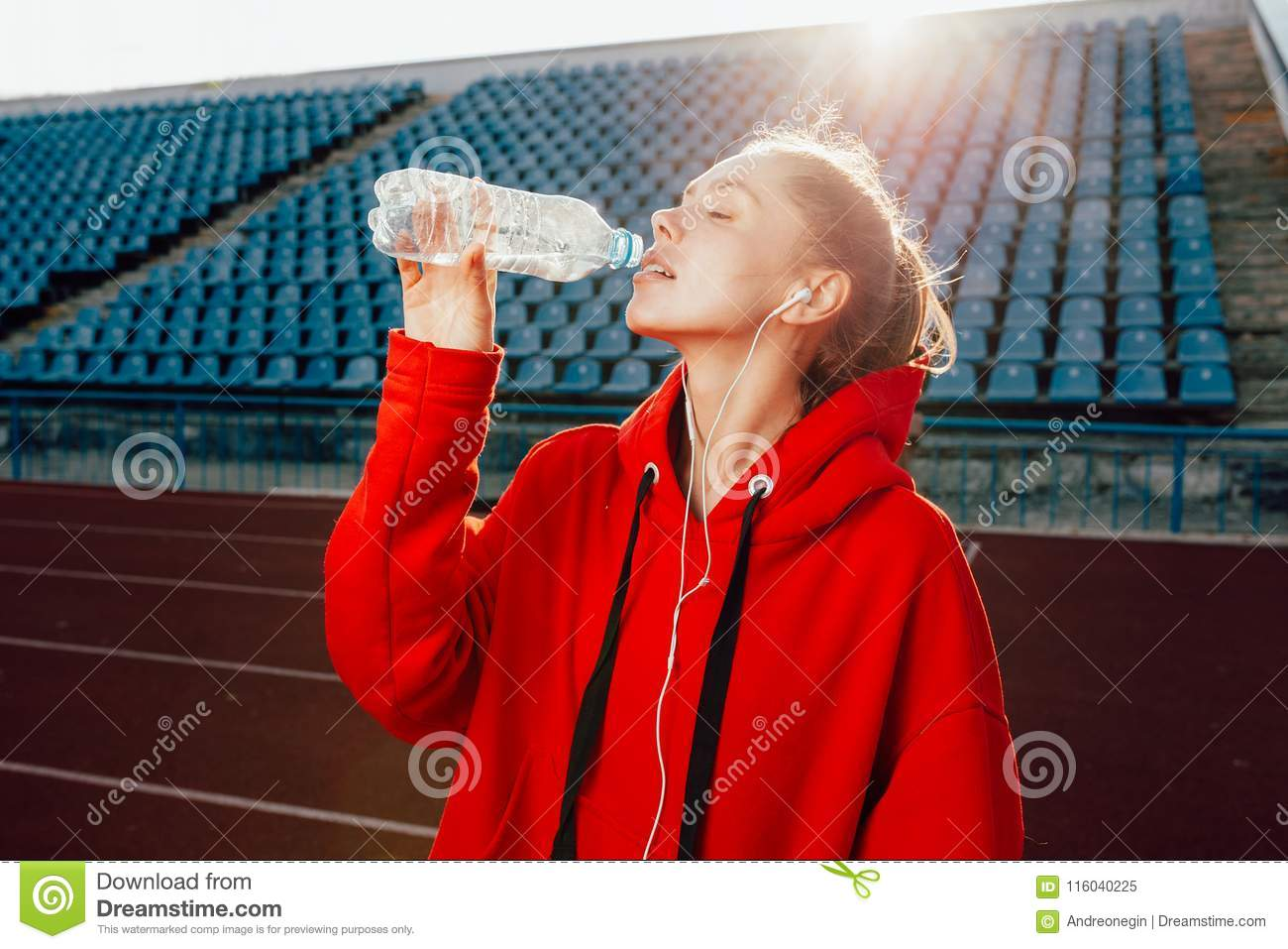 People, lifestyle and sport concept. Sport woman athlet overcame long distance, drinks water from plastic bottle, listens audio tr