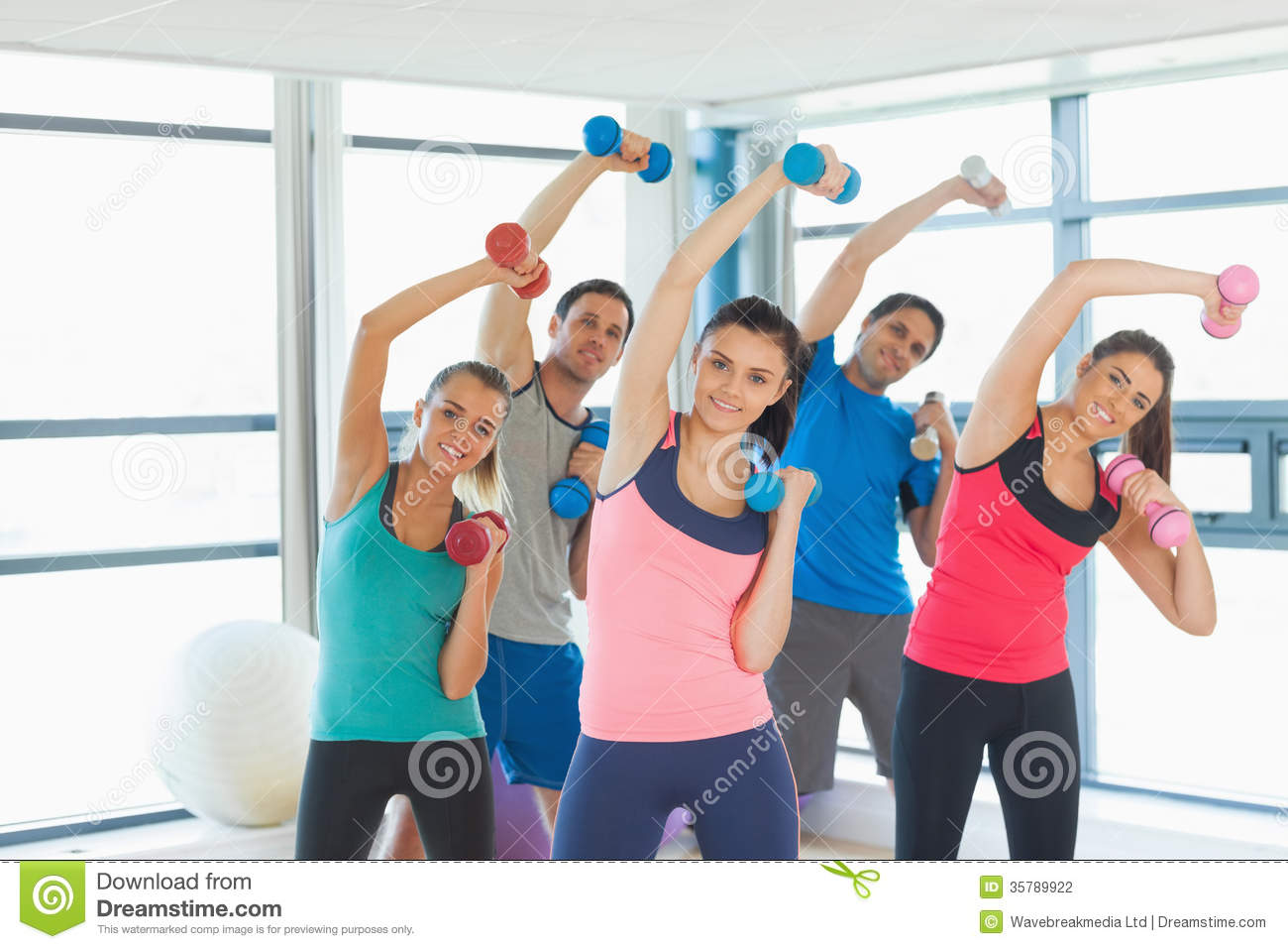 people lifting dumbbell weights with trainer in gym stock