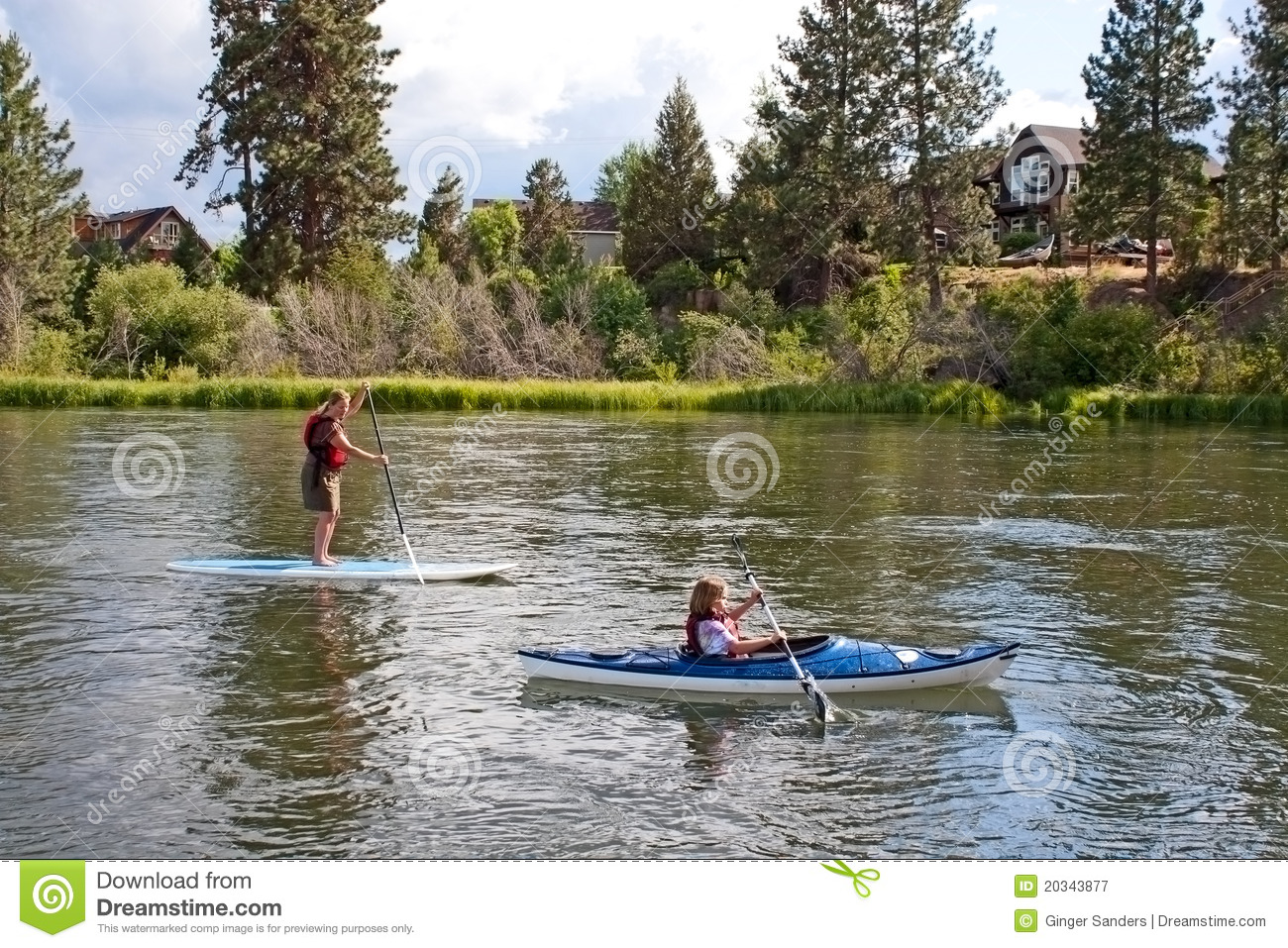 People Paddle Boarding And Canoeing In River