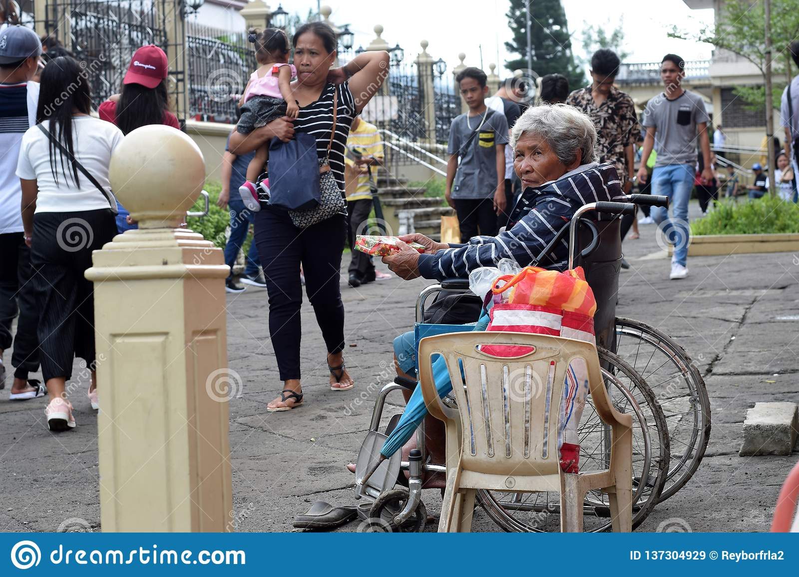 People pass by Ethnic old woman sitting on wheelchair holding Christmas gift box begging for alms at old church yard